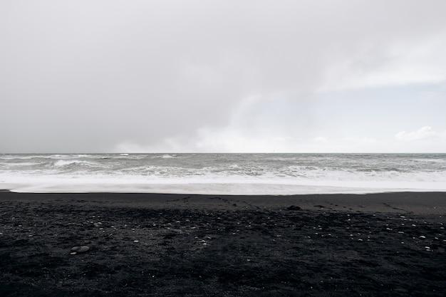 Cieli nuvolosi onde dell'oceano atlantico e sabbia nera sulla spiaggia di vik islanda