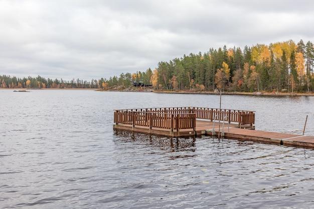 Cielo nuvoloso sopra il molo sul lago. foresta nei precedenti, svezia, fuoco selettivo di autunno