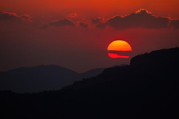 Cielo nuvoloso con il sole che sorge sopra l'orizzonte scuro nella natura estiva