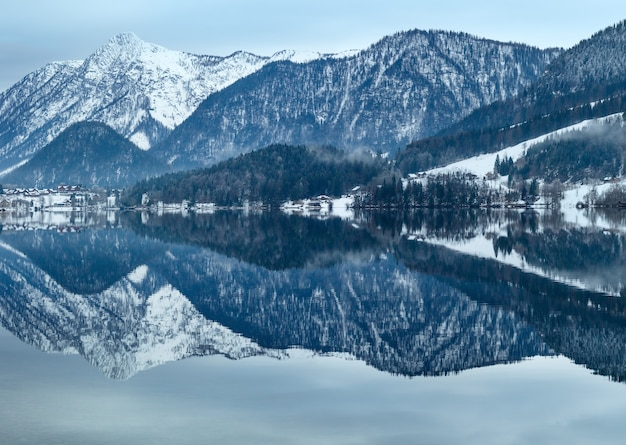 Lago alpino grundlsee (austria) di inverno nuvoloso con la riflessione fantastica del modello sulla superficie dell'acqua.