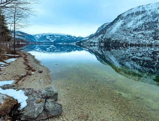 Inverno nuvoloso lago alpino grundlsee vista (austria) con fantastica riflessione del modello sulla superficie dell'acqua.