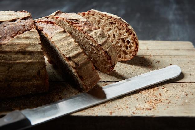 Clous up pagnotta di pane integrale a fette su tavola di pane in legno con coltello, su sfondo scuro