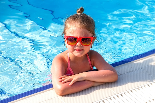 Clouse sul ritratto di una bambina felice con gli occhiali in piscina in estate