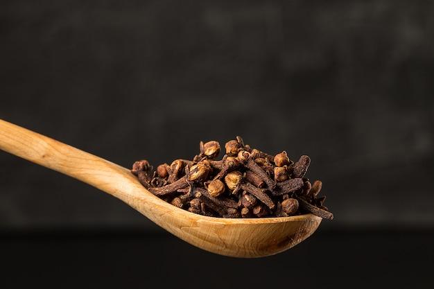 Condimento dei chiodi di garofano in una fine di legno del cucchiaio in su