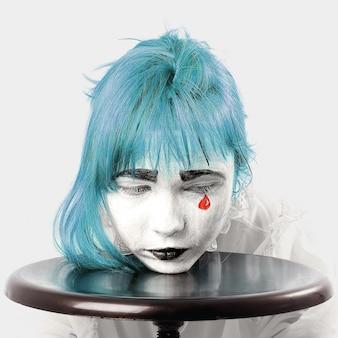 Ragazza trucco pagliaccio con capelli blu e lacrima rossa
