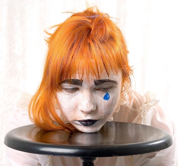 Ragazza di trucco del pagliaccio con capelli rossi e lacrima blu