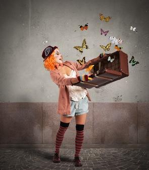 Clown apre una valigia da cui sbucano farfalle
