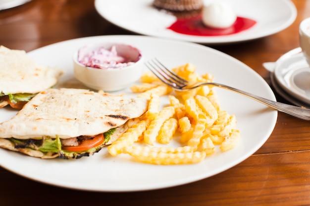 Club sandwich in pita con patate fritte e insalata