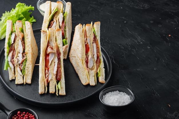 Club sandwich con carne, formaggio, pomodoro, prosciutto, su fondo nero