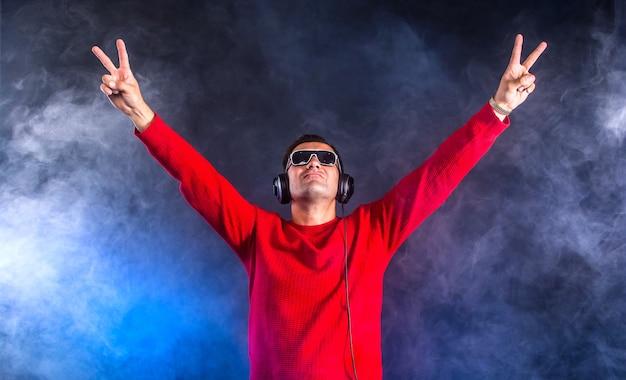 Clubber dj in cuffia con le mani in alto nel night club