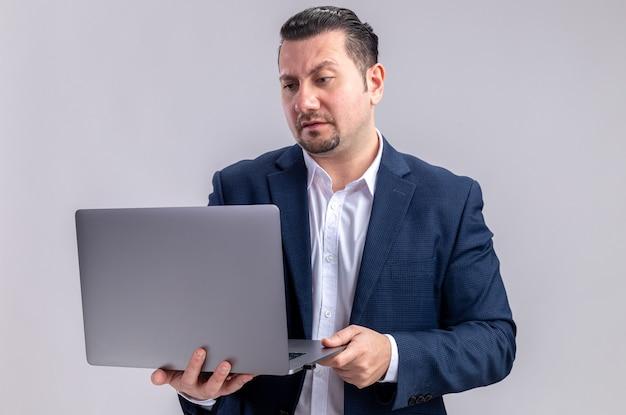 Uomo d'affari slavo adulto senza indizi che tiene e guarda il laptop