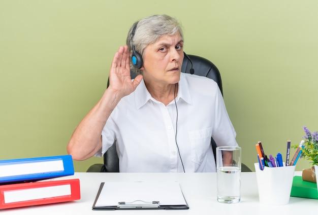 Operatore di call center femminile caucasico senza indizi sulle cuffie seduto alla scrivania con strumenti da ufficio tenendo la mano vicino al suo orecchio cercando di sentire isolato sul muro verde