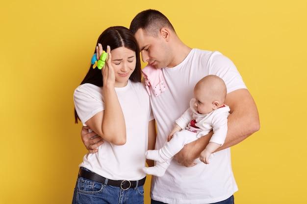 Madre e padre senza tracce con il bambino in posa isolato su sfondo giallo, le coppie tengono gli occhi chiusi, il papà si appoggia sulla testa della moglie, tenendo la figlia appena nata, mamma con il sacco di fagioli che tocca la testa con la mano.