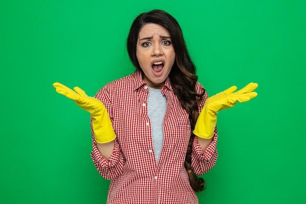 Donna pulita abbastanza caucasica senza tracce con guanti di gomma che tengono le mani aperte e guardano
