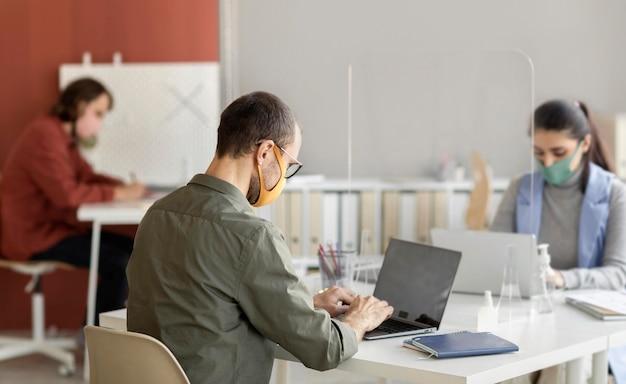 Collaboratori che indossano la maschera per il viso in ufficio