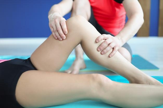 Allenatore che tiene atleta per gamba atleta in primo piano della palestra