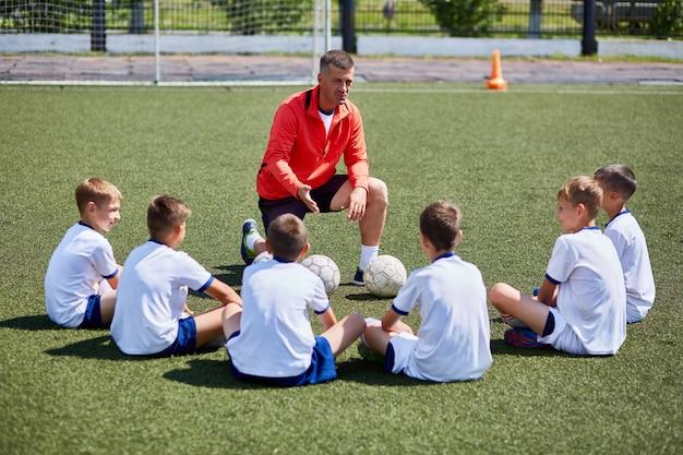 Allenatore che insegna alla squadra di calcio junior in pratica