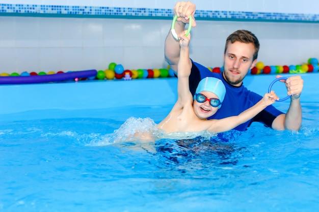 L'allenatore insegna al bambino a nuotare in piscina.