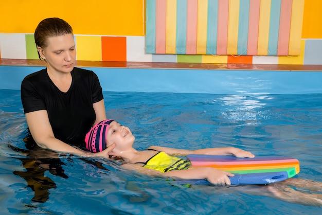 Allenatore che insegna al bambino nella piscina coperta come nuotare e fare immersioni. concetto di formazione