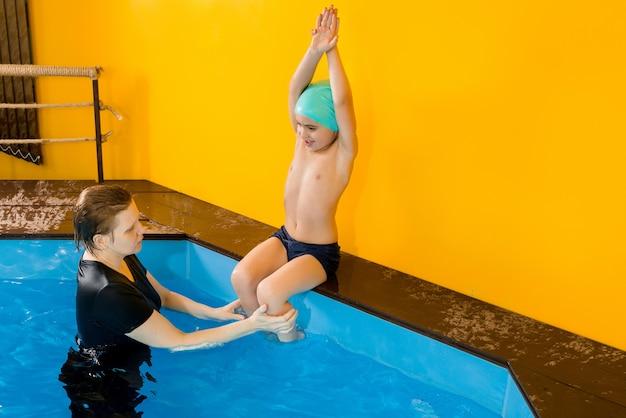 Allenatore che insegna al bambino nella piscina coperta come nuotare e fare immersioni