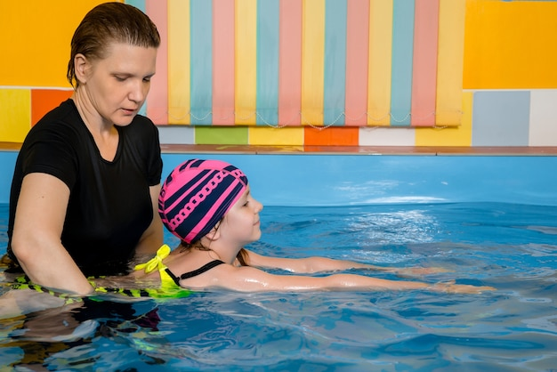 Allenatore che insegna al bambino nella piscina coperta come nuotare e fare immersioni