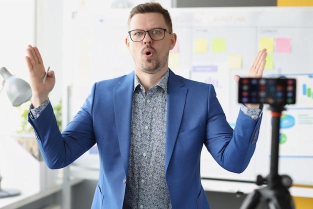 Allenatore con gli occhiali che spiega le informazioni davanti al telecomando freelance della fotocamera del telefono cellulare