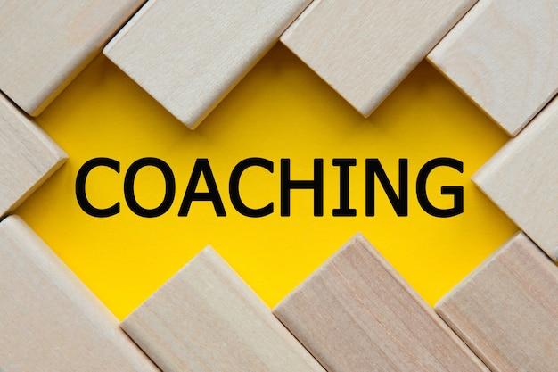 Testo coaching su sfondo giallo con cubi. una soluzione brillante per il concetto di business, finanziario, marketing. copia spazio