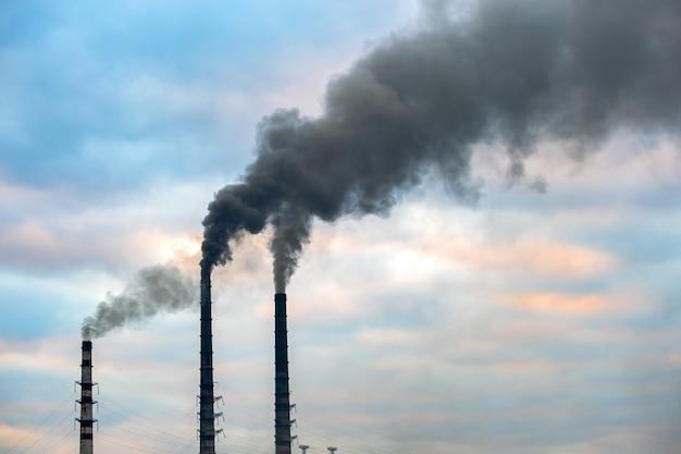 Tubi alti della centrale elettrica del carbone con fumo nero che si alza in atmosfera inquinante.