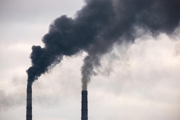Tubi alti della centrale elettrica a carbone con fumo nero che sale verso l'atmosfera inquinante.