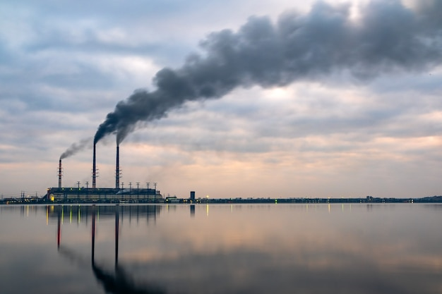 Tubi alti della centrale elettrica a carbone con fumo nero che si sposta verso l'alto atmosfera inquinante con riflessi