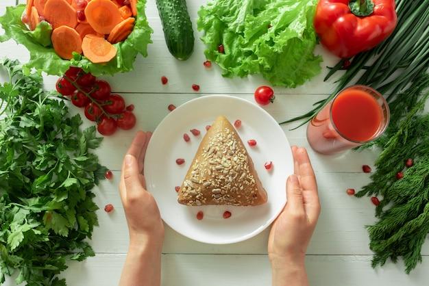 Panino grosso sullo sfondo di verdure. le mani femminili raggiungono un piatto che mostra la corretta selezione di prodotti per la perdita di peso.