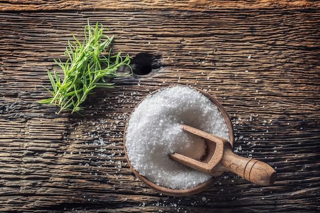 Sale a grana grossa con erbe di rosmarino in una ciotola di legno con un mestolo su un vecchio tavolo di quercia.