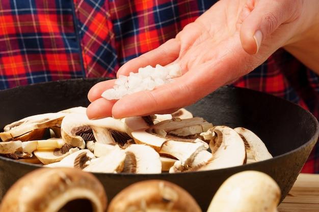 Sale grosso nel palmo della tua mano su una padella con i funghi. la ragazza sta riempiendo i funghi con i condimenti.