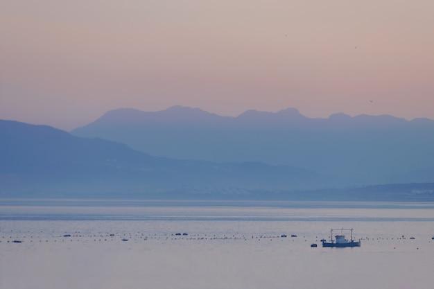 Paesaggio costiero di ceuta con barca da pesca e montagne sullo sfondo