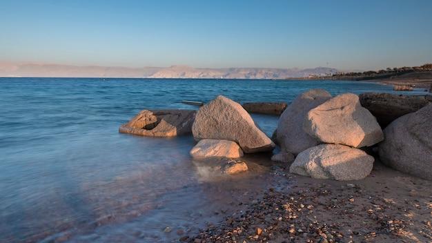 Ciottoli sulla spiaggia del sud a aqaba giordania all'alba