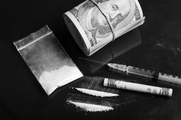 Sacchetto di plastica di cocaina, siringa con altri farmaci liquidi e pacco di dollari sul tavolo nero