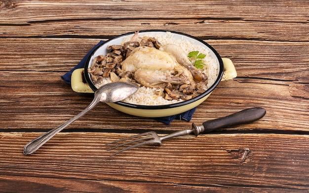 Galletto con funghi e riso in un vecchio piatto di smalto su un tavolo di legno