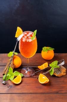 Cocktail aperol spritz e attrezzi da bar. cocktail italiano aperol spritz e un'arancia a fette su uno sfondo scuro. aperol spritz cocktail con menta fresca