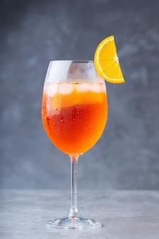 Cocktail aperol spritz. bicchiere di cocktail aperol spritz su sfondo grigio. cocktail estivo italiano con una fetta d'arancia