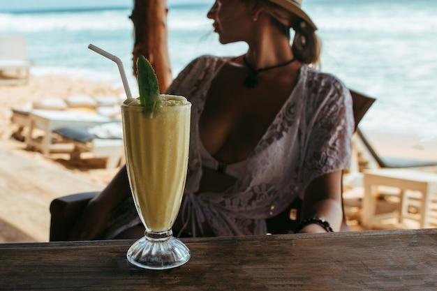 Cocktail sul bancone del bar, in sottofondo una ragazza