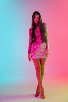 Cocktail. bella ragazza seducente in abito alla moda, vestito su sfondo rosa-blu sfumato alla luce al neon. ritratto a figura intera. copyspace per l'annuncio. estate, moda, bellezza, concetto di emozioni.