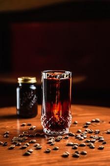 Un cocktail in un bicchiere highball collins con una lancia di ghiaccio, chicchi di caffè intorno, un barattolo di vetro con la scritta coffee beans su di esso, su un tavolo di legno, al bar.