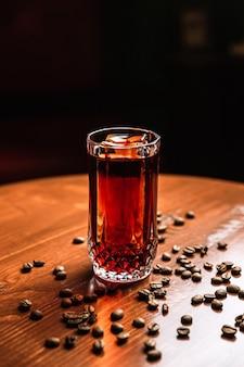 Un cocktail in un bicchiere highball collins con una lancia di ghiaccio, chicchi di caffè intorno, su un tavolo di legno, al bar.