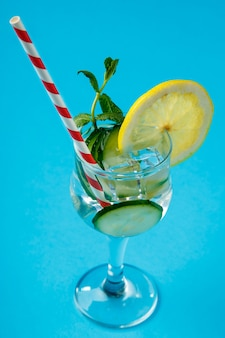 Acqua di cetriolo cocktail con limone e menta in un bicchiere su un tovagliolo su una superficie blu