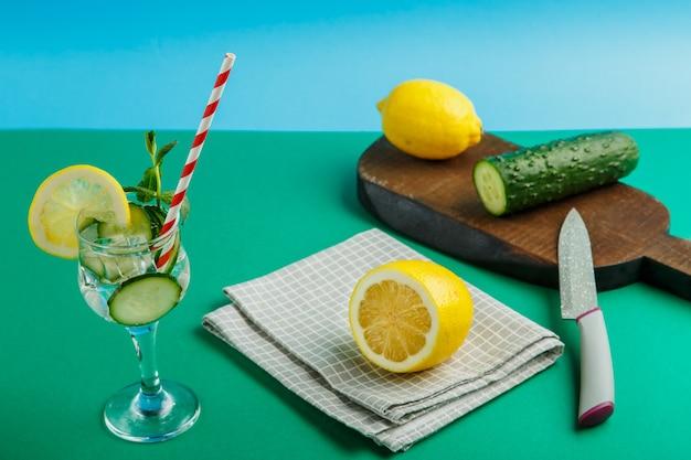Acqua di cetriolo cocktail con limone e menta in un bicchiere su un tovagliolo su uno sfondo verde accanto a un limone su un tovagliolo.