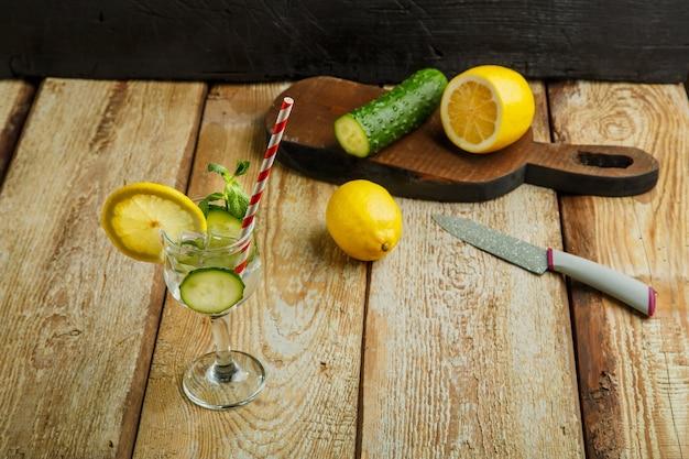 Acqua di cetriolo cocktail con limone e menta in un bicchiere su un tavolo di legno su uno sfondo nero vicino a limone e cetriolo.