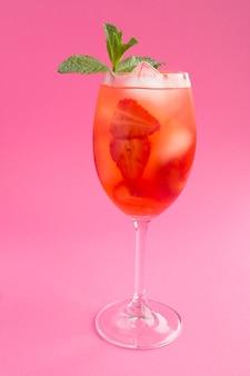 Bevanda cocktail con fragole e ghiaccio in un bicchiere sullo sfondo rosa. posizione verticale. avvicinamento.