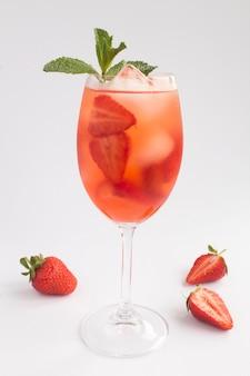 Bevanda cocktail con fragole e ghiaccio in un bicchiere su sfondo bianco. posizione verticale. avvicinamento.