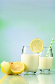 Bicchiere da cocktail decorato con limone siciliano menta e cetriolo su fondo riflettente