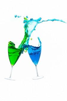 Bicchiere da cocktail con liquore colorato spruzzato a distanza ravvicinata, isolato su bianco